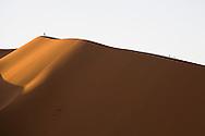 Distant hikers climbing large sand dune, Merzouga, Sahara Desert, Morocco