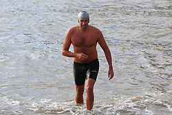 © Licensed to London News Pictures. 25/01/2015. Brighton, UK. Members of the Brighton and Hove Sea Swimming Club taking part in their daily exercise. A cold day in Brighton and the South Coast with temperatures expected to reach a maximum of 7C down the South Coast. Photo credit : Hugo Michiels/LNP