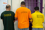 Three male inmates stand facing a wall showing their insider, listeners, mediators t-shirts in Her Majesty's Prison Pentonville, London, United Kingdom.  They are part of the national Doing Time Programme where trusted inmates offer support to new prisoners.