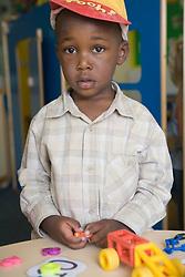 Boy at nursery school learning numeracy skills,