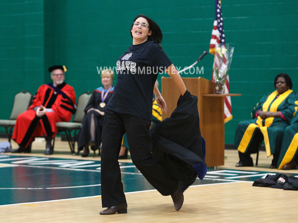 """SUNY Sullivan President Karin Hilgersom takes off her academic robe as she and other staff and faculty do a flash mob to """"Brave"""" by Sara Bareilles during convocation in the fieldhouse on Monday, Sept. 9, 2013."""