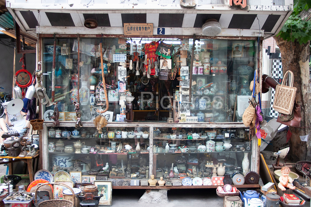 Antiques for sale at a stall on Dong Tai Road, Dongtai Lu, street market in Shanghai, China. This small area, dedicated to antiques is lined with shops and the streets covered with stalls selling artifacts from Shanghais past. There are some genuine Chinese antiques which can be very expensive. But there are also a lot of fakes for sale too, like these figures. Usually snapped up by tourists who are under the impression they are getting a bargain.
