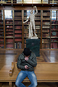 A visitor uses his phone instead of admiring the sculpture of Rondaninis Faun - a 2nd century Roman copy of a Greek original - in the Enlightenment Gallery of the British Museum, on 11th April 2018, in London, England.