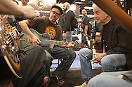 """January 21, 2016 - Anaheim, CA: World touring US bluesmen Doug Macleod (at right - black jacket, jeans) and Nathan James (at left - hat, glasses) at the National Resophonic booth during the NAMM Show, an annual trade show organized by the The National Association of Music Merchants (NAMM). <br /> <br /> The largest of its kind, NAMM features music instruments and products of every imaginable music-related item. National Resophonic was started in 1989 by Don Young and McGregor Gaines in a garage in Long Beach, CA. The two resurrected the legendary guitar company National String Instrument Corporation originally founded in 1927 by the Slovakian born John Dyoperra. These instruments called """"resonator guitars"""" were steel bodied with built in speaker cones that projected loud sound, good enough for live performances. Their unique sound became the preferred instrument of blues, Hawaiian and hillbilly musicians of the 1930s and are iconic of these musical genres. National went out of business in the 1950s due to the invention of the electric guitar. In 1990, Young and Gaines formed National Resophonic, a new company in San Louis Obispo, CA that produced excelent modern versions of the older guitars. Their guitars are in very high demand worldwide among guitarists from street performers to famed musicians like Keb' Mo', Bonnie Raiit, John Mellencamp and Eric Clapton. National currently produces nearly 2700 instruments per year, representing more than 50 different models. The waiting list to order one of their guitars can be several months. Young and Gaines sold their interests in the company which it is now owned by Eric Smith, an emplyee of National for 24 years. Sadly, Don Young passed away on June 15, 2016. (Torin Boyd/Polaris)."""