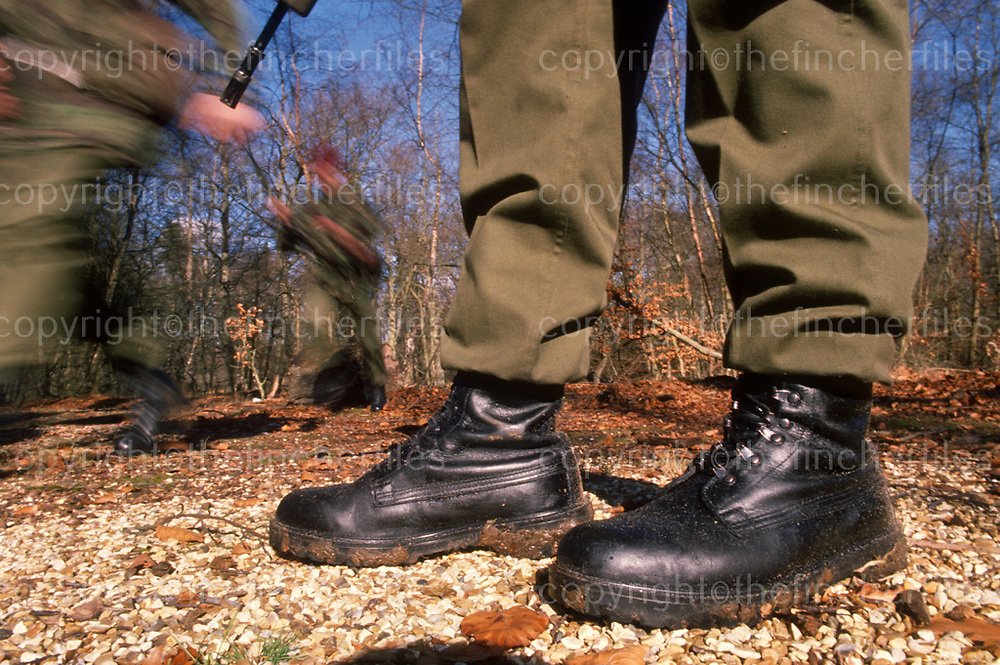 The standard issue British army combat boot. In the background, soldiers of the Parachute regiment in the midst of a training exercise. Photograph by Terry Fincher