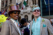 New York, NY - April 16, 2017. Two men with elaborate hats at New York's annual Easter Bonnet Parade and Festival on Fifth Avenue. One of the hats is a wire basket holding a number of naturally-colored eggs. (There are seven breeds of chickens that lay colored eggs.)