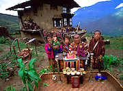 Nalim and Namgay's family of Bhutan, with all of their possessions. The family of subsistence farmers lives in a 3-story rammed-earth house in the hillside village of Shingkhey, Bhutan. Namgay, who has a hunched back and a clubfoot, grinds grain for neighbors with a small mill his family purchased from the government. They are paying for the mill as they can (often the payment is made in grain and mustard oil). Namgay is also a reader of sacred texts and conducts house cleansing and healing ceremonies for their 14-house village.(Material World pages 72-73)