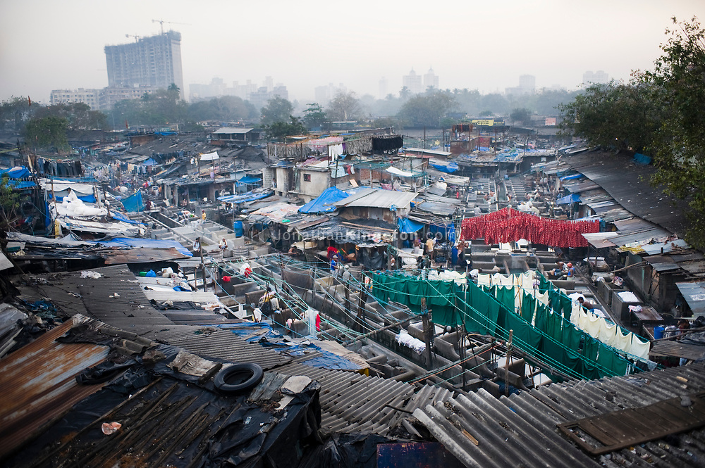 The Mahalaxmi Dhobi Ghat in Mumbai, India.  At the ghat 10,000 workers wash over 1,000,000 pieces of clothing a day, by hand, each individual standing in the soapy water near their washing stone for up to 16 hours.  The dhobi ghat is one of the largest  examples of this profession in the world and it is finding itself at the center of a a John Henry-esque story of  man versus machine is unfolding in this rapidly growing city of over 18 million people.