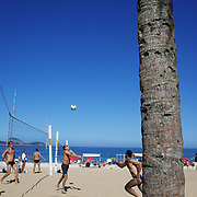 Locals play beach volleyball at Ipanema beach, Rio de Janeiro,  Brazil. 4th July 2010. Photo Tim Clayton..The beaches of Rio de Janeiro, provide the ultimate playground for locals and tourists alike. Beach activity is in abundance as beach volley ball, football and a hybrid of the two, foot volley, are played day and night along the length and breadth of Rio's beaches. .Volleyball nets and football posts stretch along the cities coastline and are a hive of activity particularly at it's most famous beaches Copacabana and Ipanema. .The warm waters of the Atlantic Ocean provide the ideal conditions for a variety of water sports. Walkways along the edge of the beaches along with exercise stations and cycleways encourage sporting activity, even an outdoor gym is available at the Parque Do Arpoador overlooking the ocean. .On Sunday's the main roads along the beaches of Copacabana, Leblon and Ipanema are closed to traffic bringing out thousands of people of all ages to walk, run, jog, ride, skateboard and cycle more than 10 km of beachside roadway. .This sports mad city is about to become a worldwide sporting focus as they play host to the world's biggest sporting events with Brazil hosting the next Fifa World Cup in 2014 and Rio de Janeiro hosting the Olympic Games in 2016...
