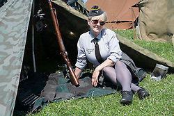 A female re-enactor portrays a Wehrmacht Heferin with the German Army in work uniform blouse shelters from the sun in the shade of a Zeltbahn. Wehrmacht Heferinnen were he German Armed Forces female Auxiliaries. At various periods o time during world war two they were sometimes classified as military personnel other times as uniformed civilians employed by the German Armed Forces (Wehrmacht)<br />  <br /> 04 July 2015<br />  Image © Paul David Drabble <br />  www.pauldaviddrabble.co.uk