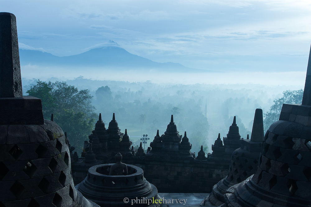 Stupas with volcano Merbabu capped in clouds in the background, Borobudur, Kedu Valley, South Central Java, Java, Indonesia, Southeast Asia