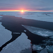 The sun sets over the broken, thin ice of the Arctic Ocean.