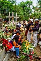 A family at the grave of a loved one (with a band playing for them), Day of the Dead (Dia de Los Muertos), November 2, Municipal Cemetery, Morelia, Michoacan, Mexico.
