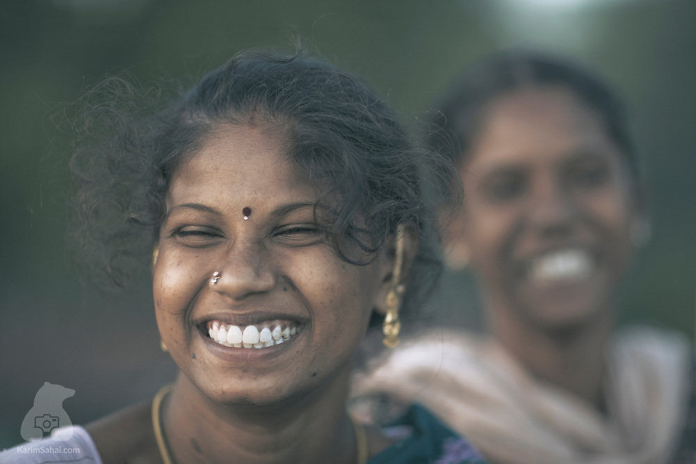 A young south indian woman and her sister laugh after hearing a joke.