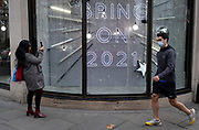 After a bleak year of Coronavirus pandemic misery, shoppers in Knightbridge walk past the temporary Christmas-themed Harvey Nichols window which urges Londoners to be optimistic for the coming year, on 12th November 2020, in London, England.
