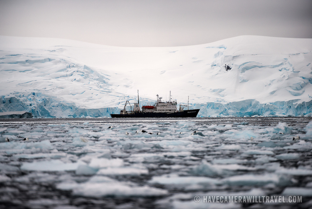 The Polar Pioneer, an Antarctic cruise ship, lies still near the shore in Curtis Bay, Antarctica, past the brash ice floating on the water in the foreground.