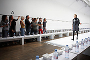 Girl model rehearses before design team before British couture designer Margaret Howell's Autumn fashion show in design studio