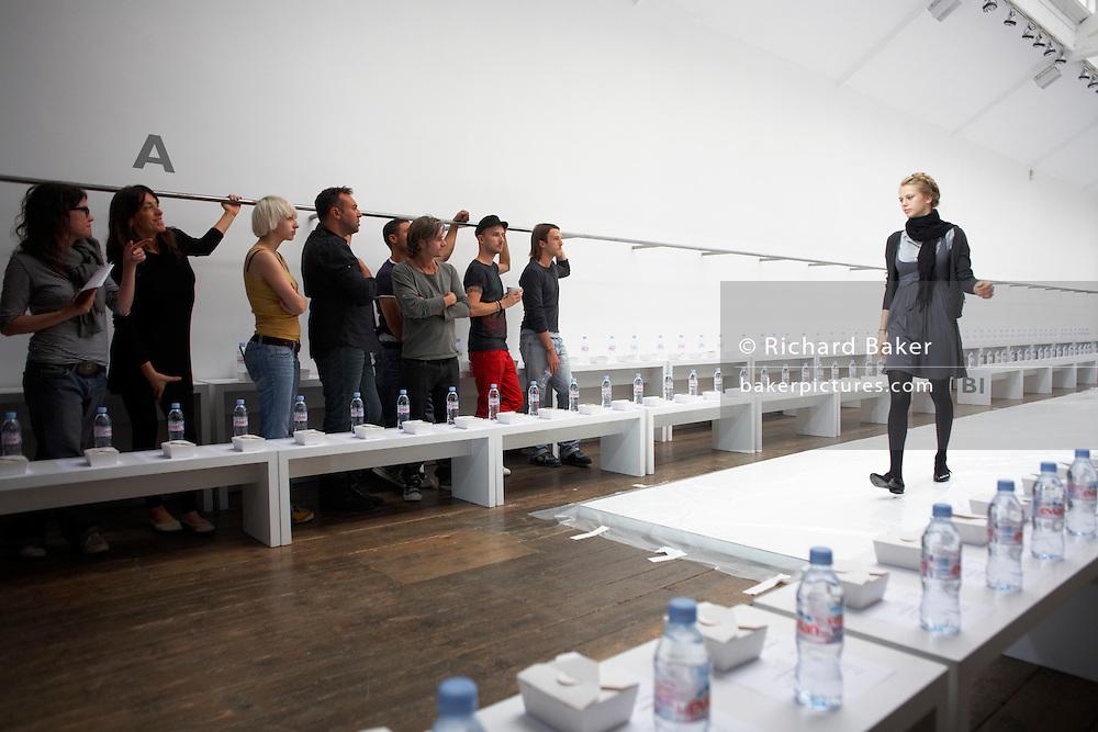 Girl model rehearses before design team before British couture designer Margaret Howell's Autumn fashion show in design studio