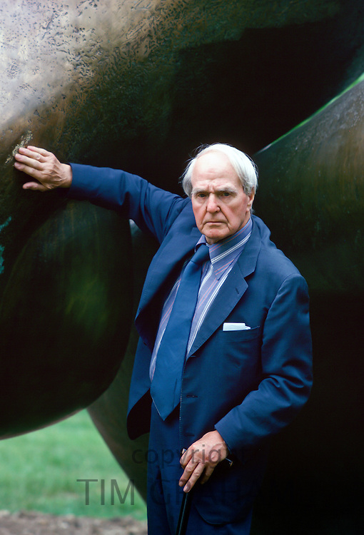 Sculptor Henry Moore standing by his 'Sheep Piece' sculpture, England, United Kingdom