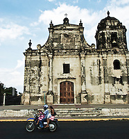 A typical sight in the streets of Nicaragua. A family of 3 (or sometimes 4-5) all sharing a ride on a 200cc moto. The deteriorating exterior of La Iglesia San Juan Bautista sets the backdrop.
