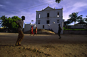 People passing by Our Lady of Health Church in Ilha de Mozambique. This church is build on the separation betweeen colonial Stone City and Macuti Town, where most of islands population lives