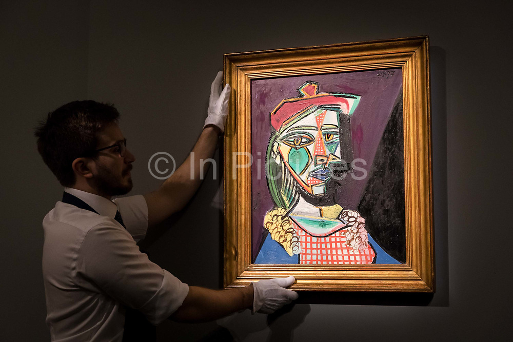 A member of staff holds Femme Au Beret Et a La Robe Quadrillee - Marie-Therese Walter by Pablo Picasso, on February 22nd, 2018 at the preview for Sothebys upcoming Impressionist, Modern and Surrealist Art auction at Sothebys in New Bond Street, London, England.