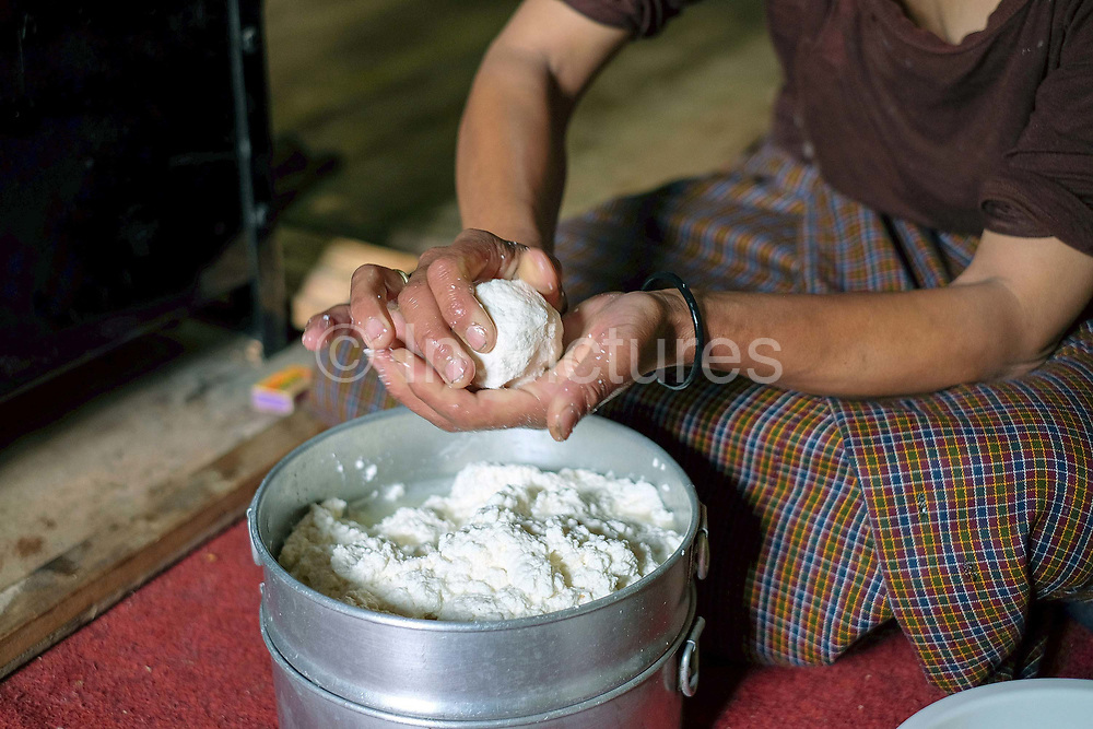 Phublham making 'datse', a small handmade cheese made from cow's milk in her farmhouse kitchen, Bayta village, Phobjikha valley, Bhutan. Datse is used in almost every Bhutanese dish including the national dish 'ema datse', chillies with cheese.