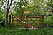 As the UKs Coronavirus pandemic lockdown continues into its 5th week, and UK deaths from Covid-19 reached 21,678 - a daily rise of 586, a gate is taped-off while seasonal rain empties Ruskin Park in Lambeth, where until now, this green space in south London has been busy with those exercising according to social distance requirements, on 28th April 2020, in London, England.