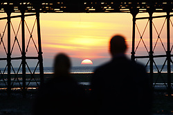 © Licensed to London News Pictures. 10/10/2018. Worthing, UK. A couple watch as the sun rises behind Worthing pier on a day when unseasonably high temperatures expected in parts of the UK. Photo credit: Peter Macdiarmid/LNP