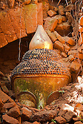The top of the head of an ancient buddha statue, poking above the rocks of the ruins it now stands in at the Shwe In Dein pagoda complex near Inle Lake, Myanmar