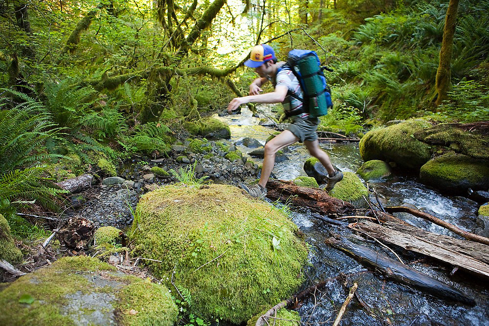 Hiker Hamilton Boyce hops mossy boulders as he crosses a creek along the Eagle-Benson Trail, Columbia River Gorge National Scenic Area, Oregon.