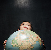 Young boy holding globing looking up