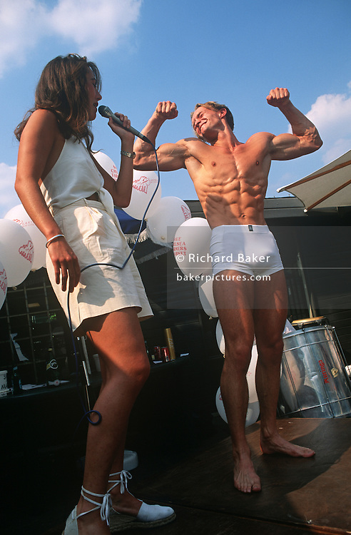 The Mr Chelsea Body Beautiful talent competition is held on the Kings Road in London. Entrants are handsome males and girls showing their muscles and well-trimmed bodies. We see hairy chests, pectorals and biceps on-show by these young exhibitionists who parade themselves in the open-air. Slightly behind them there are also two elderly ladies looking like sisters or perhaps twins. They were once beautiful themselves and sit eagerly on a bench against a wall peering at the handsome young men, wishing they were young again. One holds a walking stick and the other grasps a bottle of wine. It is a scene of young and old, of youth and ageing beauty.