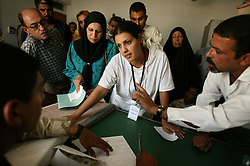 Alyaa Abdul Hassan Abbood, 23, translator, mediates as Iraqi civilians wait for monetary compensation for damages done by U.S. troops at a court in Baghdad, Iraq, Sept. 27, 2003.