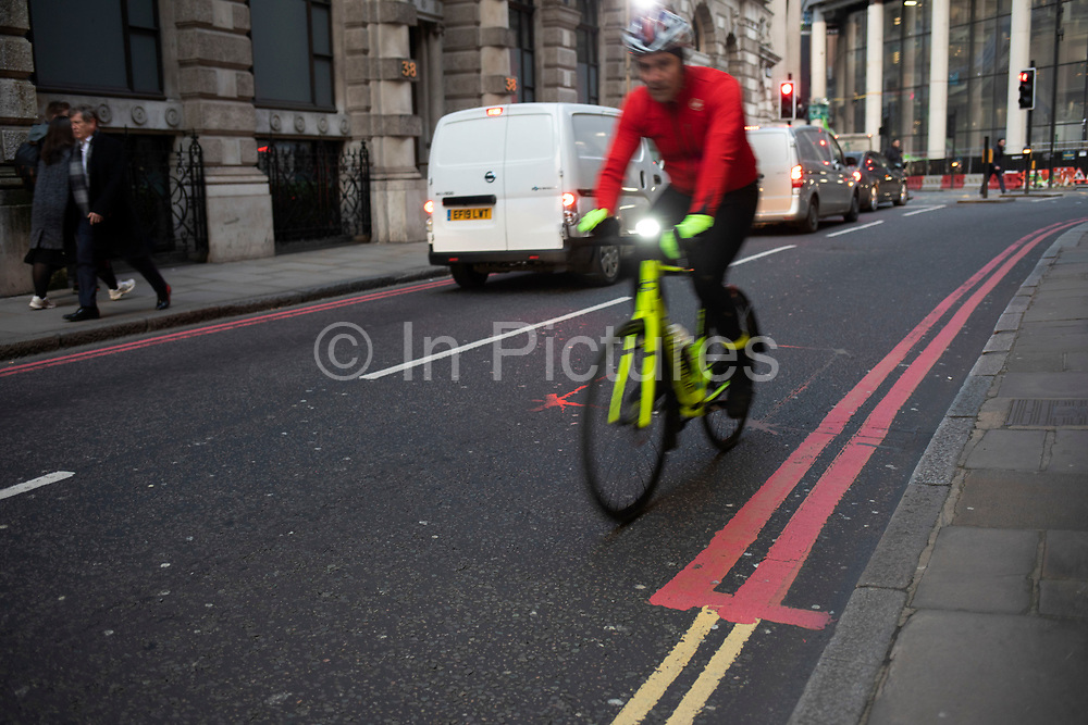 Cyclist passes red and yellow double lines in the City of London on 5th February 2020 in London, England, United Kingdom. A double yellow line is a painted marking separating two lanes of a road. It consists of two parallel, solid yellow lines, and its presence usually indicates a no-passing restriction or no passing zone, where crossing the line is prohibited. Red routes are marked with red lines at the sides of the road. Double red lines mean that the regulations apply at all times and on all days, including no stopping. Single red lines means that the prohibition applies during times displayed on nearby signs or at the entry to the zone.