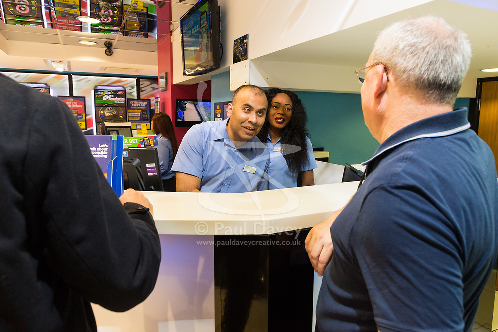 Betting Shop Manager-of-the-Year finalist Amran Al-Haque and Deputy Manager Elaine Norbert talk to one of his customers at Coral, 1 Canada Square, Canary Wharf, London, November 08 2018.