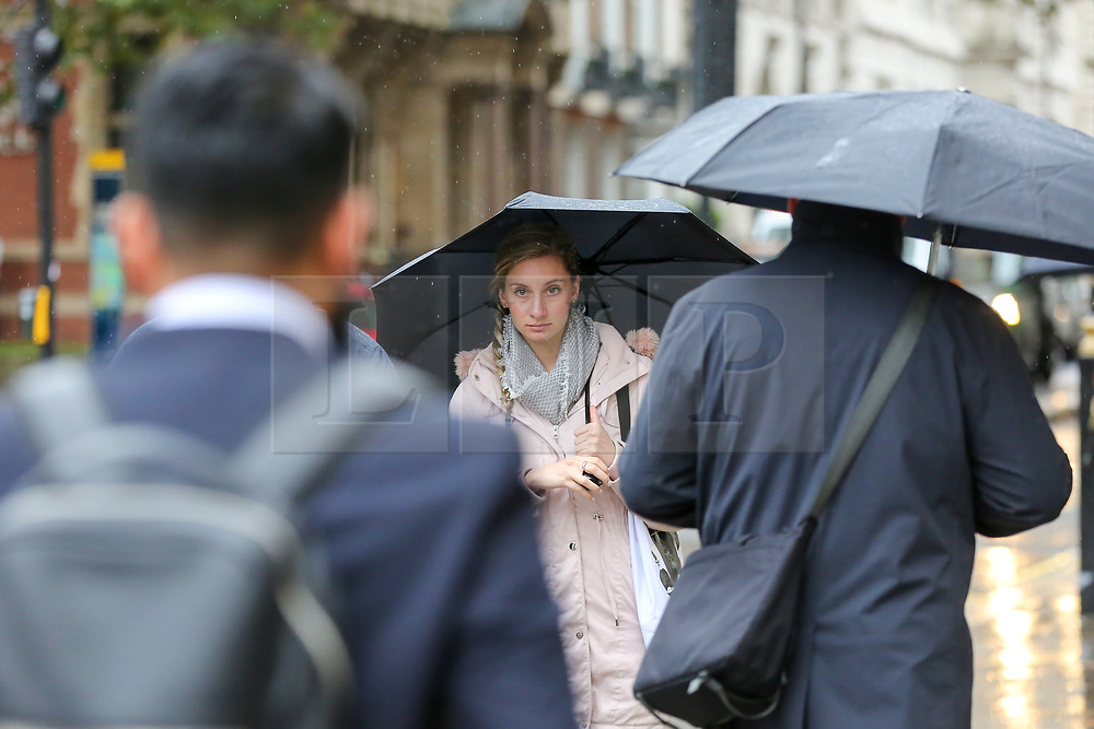 © Licensed to London News Pictures. 21/10/2019. London, UK. Members of the public shelter from rain underneath umbrellas on a wet and cold day in Westminster, London. Photo credit: Dinendra Haria/LNP