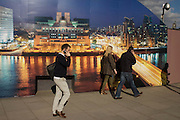 Londoners on smartphone calls walk past a CCTV camera and a construction hoarding - a night time panorama of the Thames south bank, featuring the HQ of the intelligence service (MI6) across the river in Vauxhall.