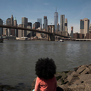 People relax at Brooklyn Bridge Park in Brooklyn, New York on April 10, 2017. John Taggart for The New York Times.