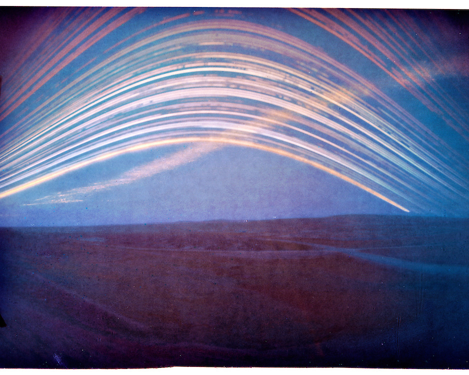 Highway 22 and highway 1A intersection in Cochrane. A 6 month long exposure. From winter solstice (lowest arc in the sky) till summer solstice (highest arc). Made with a DIY pinhole camera and a piece of photographic paper.