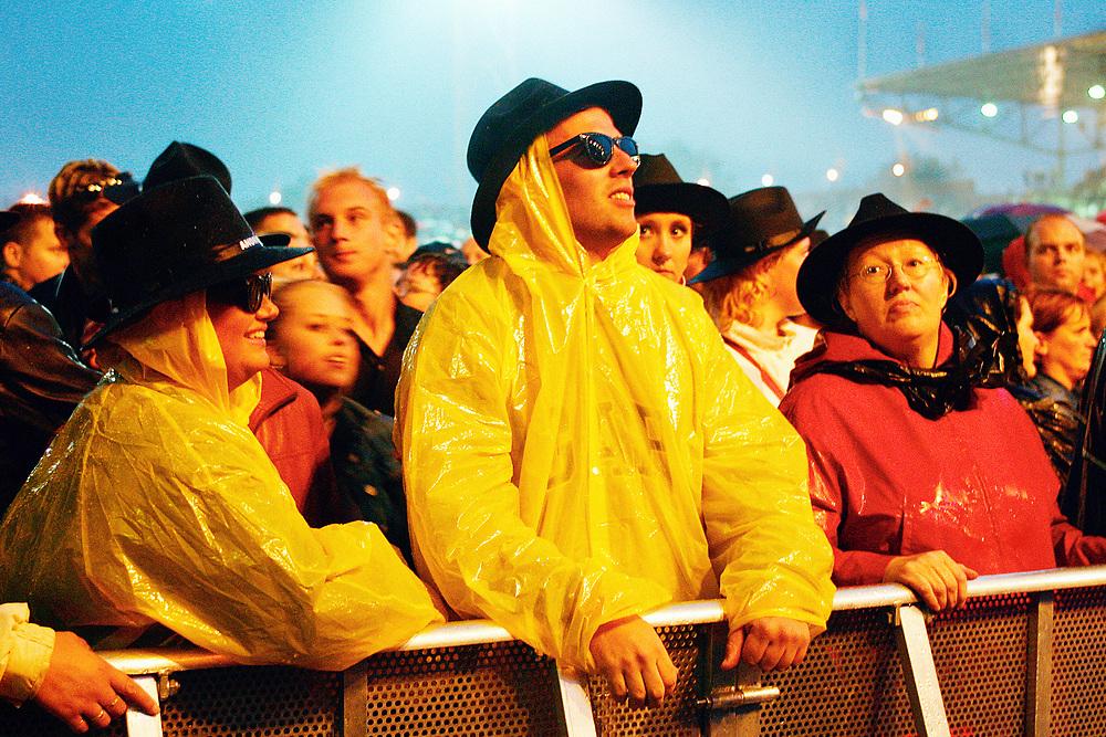 Nederland. Amsterdam, 24-08-2002. Foto: Patrick Post <br /> Muzikant/ zanger Andre Hazes tijdens zijn optreden in een uitverkocht  Olympisch Stadion. De fans ,velen met Hazeshoed, werden overspoeld door hevtige regenbuien die voor een erg drassige ondergrond zorgde. Vele fans waren doorweekt, andere hadden een poncho of regenjas meegenomen.