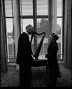 "Presentation of Harp to President DeValera..1972..29.12.1972..12.29.1972..29th December 1972..Mrs Julia Fennell presented a harp to President DeValera as a gift to Áras an Uachtaráin. She presented the harp on behalf of her late husband Mr Thomas J Fennell and herself..The harp was manufactured in 1835 at the firm of Robinson and Russell,westmoreland Street,Dublin. the harp is 36ins high and has 33 strings. It will be retained in an exhibition case bearing the inscription ""Tomas O'Fionnghaill agus Sile Ui Fhionnghail,Baile Atha Cliath, a bhronn ar Áras an Uachtaráin,1972"".(Presented to Áras an Uachtaráin by Thomas and Julia Fennell,Dublin 1972)..Picture shows President DeValera positionong the harp in a prominent position within Áras an Uachtaráin. Mrs Fennel looks on approvingly."