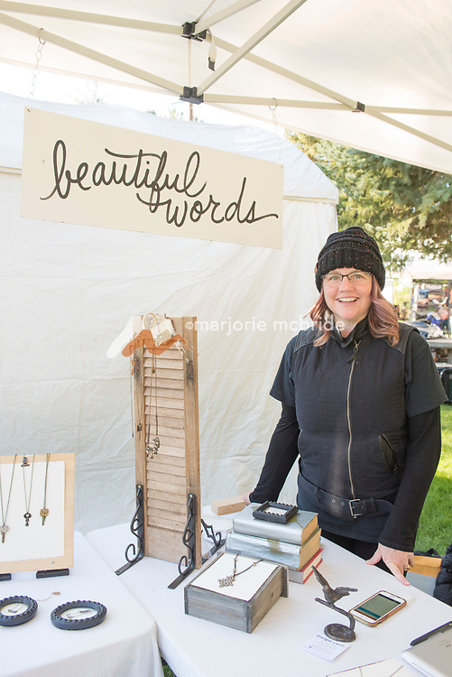 """Artist Jodi Miller smiles while standing at her jewlery booth """"Beautiful Words"""" during the Thousand Springs Art Festival at Ritter Island near Hagerman, Idaho. VMR"""