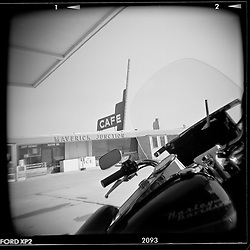 Maverick Junction. Riding to Sturgis, 1999<br /> <br /> Limited Edition Print from an edition of 50. Photo ©1999 Michael Lichter.<br /> <br /> The Story: Truck stops and cafes help me remember my travels.  The journey blends together in a swirl of images and memories but the truck stop is frozen in my mind. I put four gallons in the tank, park and go in for a chicken fried steak. The waitress's twang and variations in the menu give me a flavor for the land.