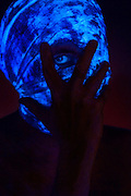 Blacklight portrait of a man's head wrapped in glowing blue gauze with an eye peaking out from between his fingers.