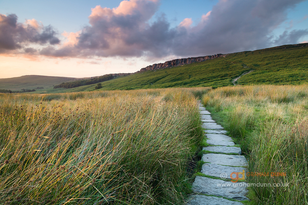 The path from Hook's Car to Stanage Edge's 'Popular End'. High Neb can be seen in the distance. Peak District National Park, Derbyshire, England, UK. Summer.
