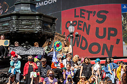 """© Licensed to London News Pictures. 25/08/2021. LONDON, UK.  Climate activists from Extinction Rebellion protest in Piccadilly Circus.  The event is part of the 'Impossible Rebellion' protest to """"target the root cause of the climate and ecological crisis"""" and are ongoing for two weeks until the Government agrees to stop all new fossil fuel investments.  Photo credit: Stephen Chung/LNP"""