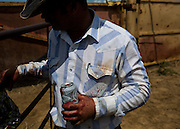 Curt McCuistion of Sugar City, Colo. takes a break during a branding on Gray's Ranch in Crowley County, Colo. on June 1, 2016. During the day 260 calves will be wrangled, branded, vaccinated and tagged. Males are castrated to prevent them from becoming aggressive as they get older. Ranchers in the area rely on each other to help with brandings, which are also a social event in the rural county.
