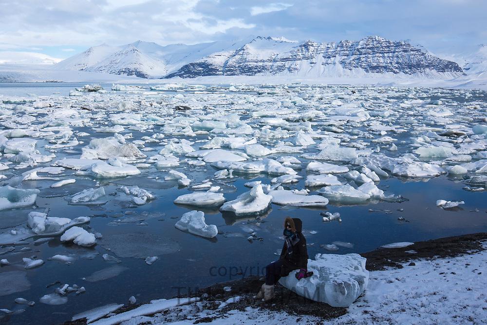 Woman tourist sits on ice block at Jokulsarlon glacial lagoon, Vatnajokull National Park, South East Iceland