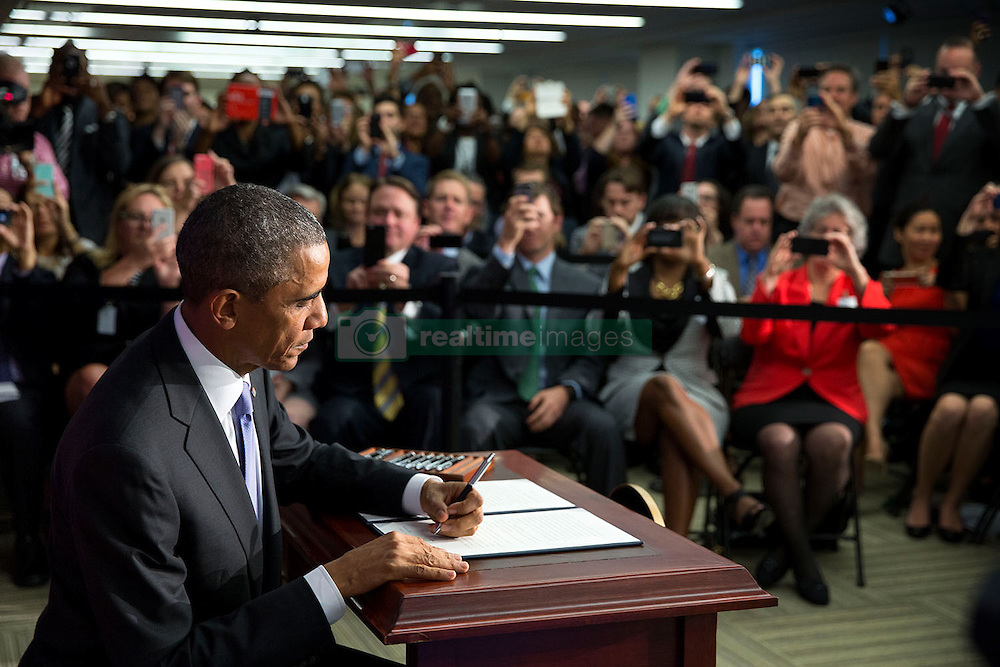 """President Barack Obama signs Executive Order """"Improving the Security of Consumer Financial Transactions,"""" at the Consumer Financial Protection Bureau in Washington, D.C., Oct. 17, 2014. (Official White House Photo by Pete Souza)<br /> <br /> This official White House photograph is being made available only for publication by news organizations and/or for personal use printing by the subject(s) of the photograph. The photograph may not be manipulated in any way and may not be used in commercial or political materials, advertisements, emails, products, promotions that in any way suggests approval or endorsement of the President, the First Family, or the White House."""